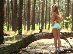 Длинноногая блондинка позирует голой на природе в лесу