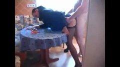 Жена в строгом костюме развлекается с мужем на кухне